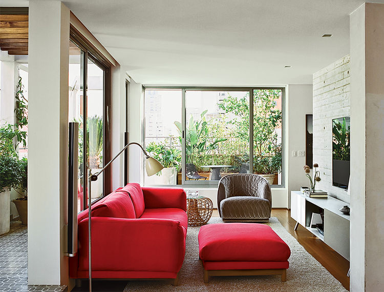 São Paulo apartment living room with red Muuto sofa, Moroso armchair, and Vitra storage unit