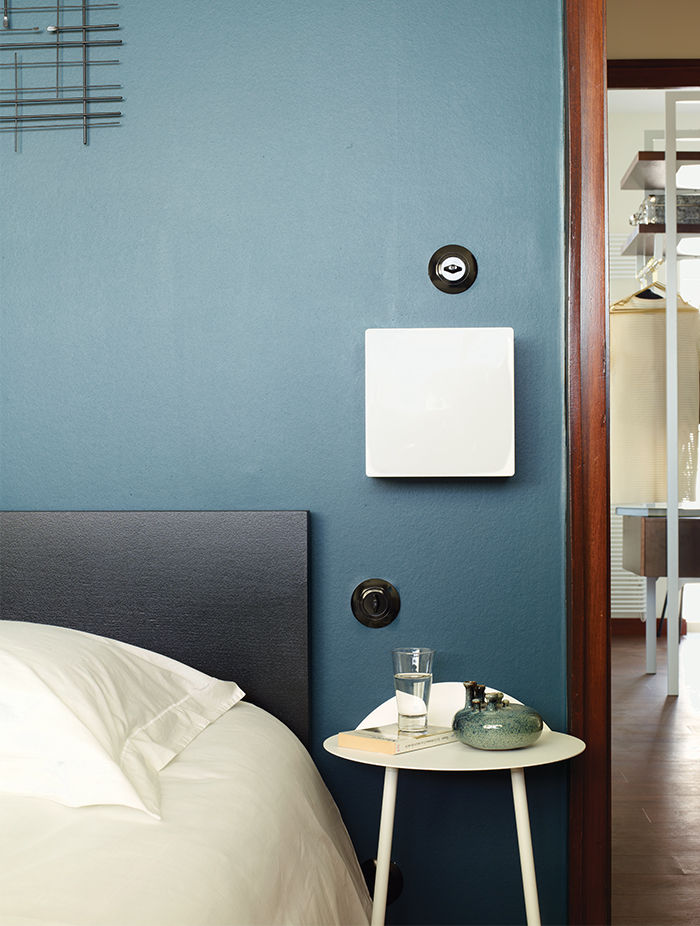 French bedroom with blue walls and 1970s sconce