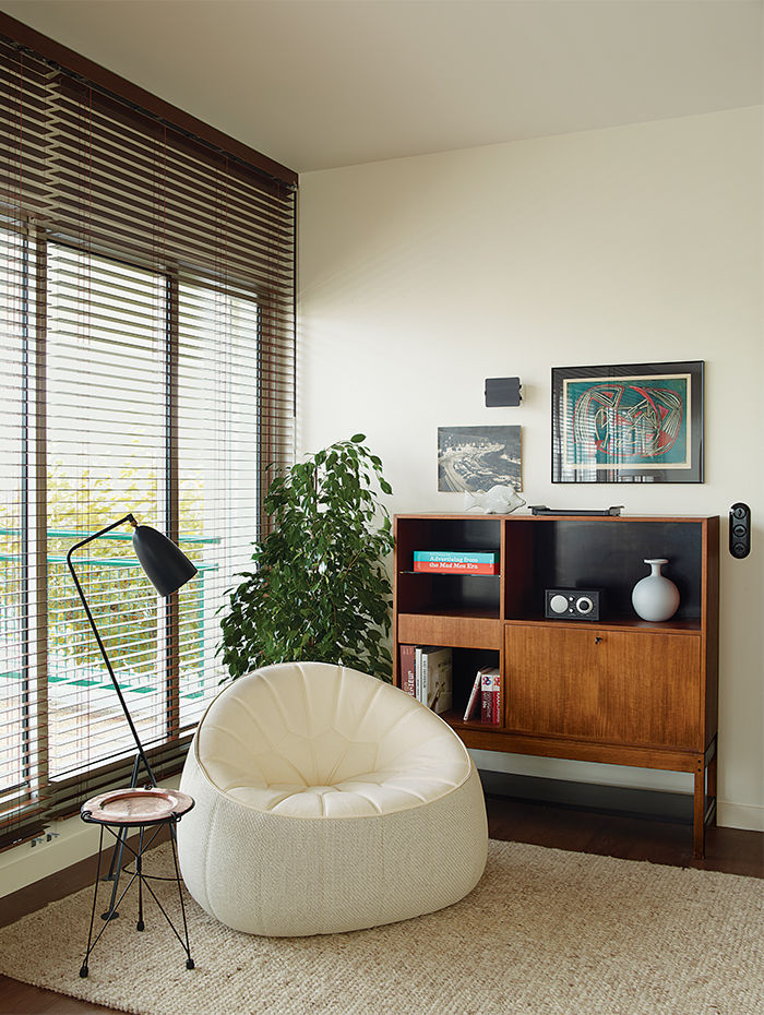 Living room with Noé Duchaufour-Lawrance chair, Charlotte Perriand wall sconce, and Greta Grossman floor lamp