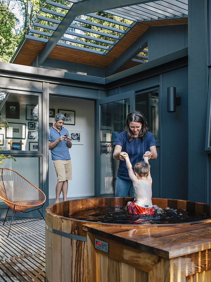 Hot tub nestled in wood deck in midcentury Portland home