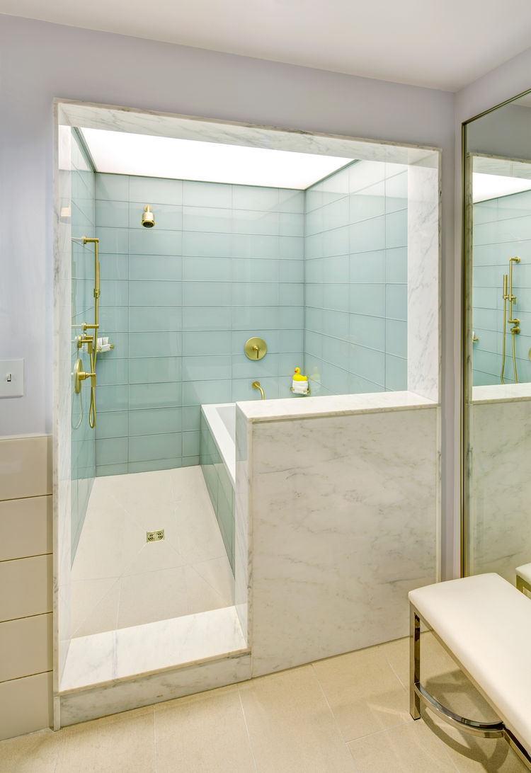 Marble shower lined in glass tile with gold fixtures in 21c Museum Hotel