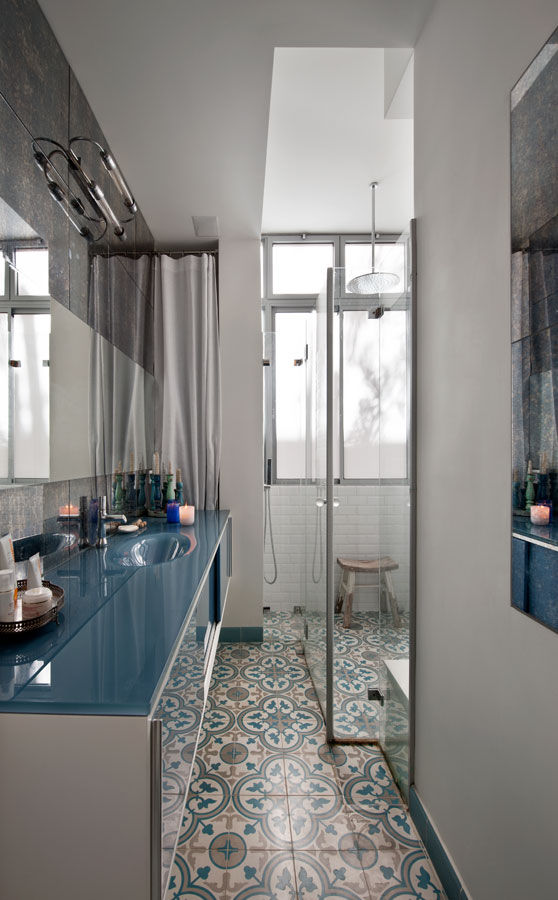 Tel Aviv bathroom with tiled floor and blue glass cabinet