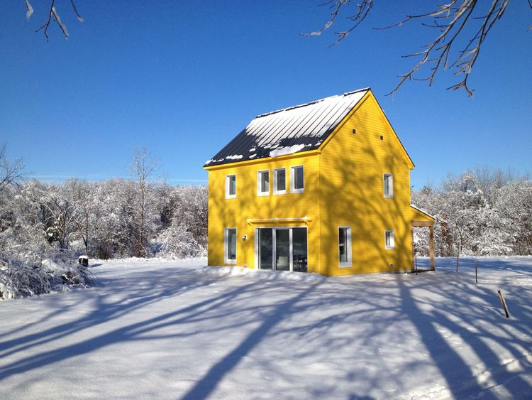 Yellow Passive house that runs on solar power