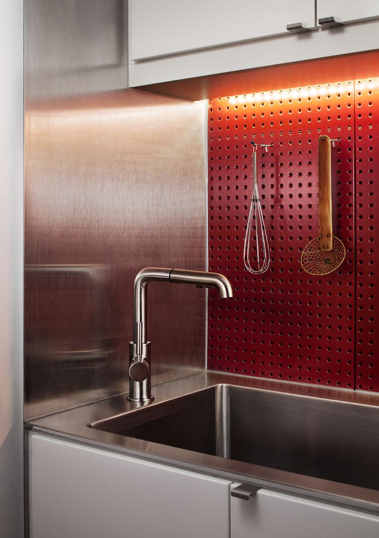 Red steel pegboard backsplash for hanging utensils