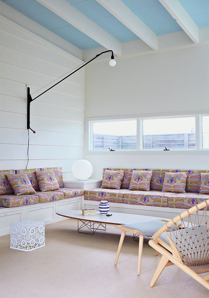 Fire Island living area with built-in sofa and Wire Base Elliptical Table by Charles and Ray Eames