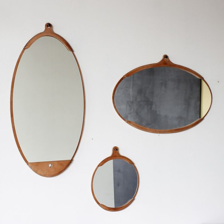 Rustic wall mirror with hand-stitched leather frame