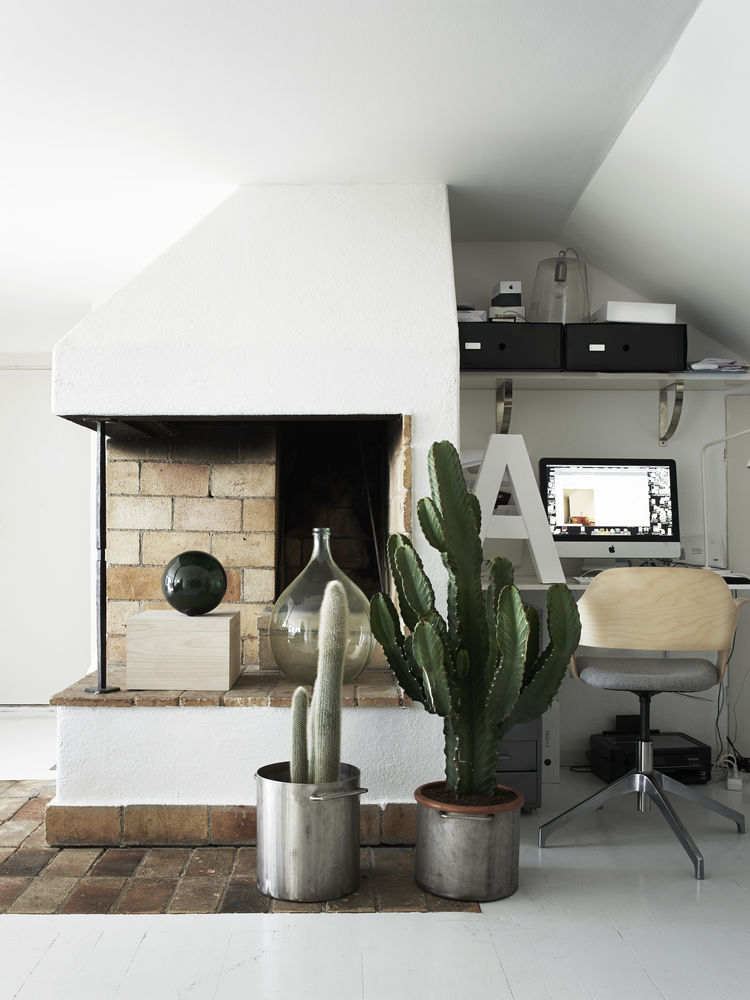 brick fireplace with cacti and desk