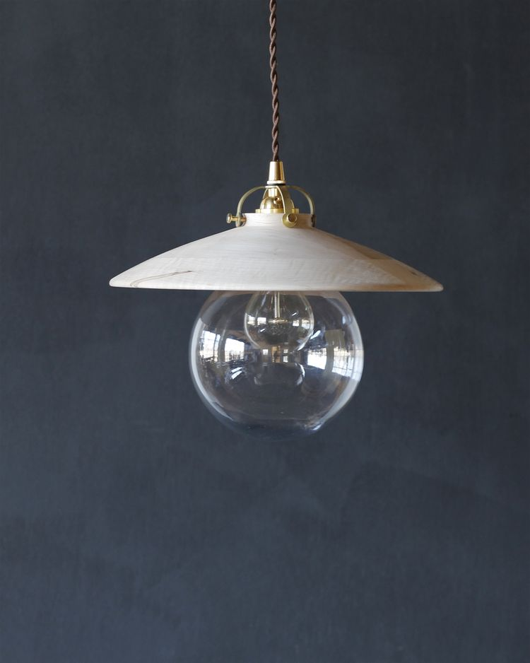 Minimalist pendant comprised of hand-turned wood, glass, and brass fixings