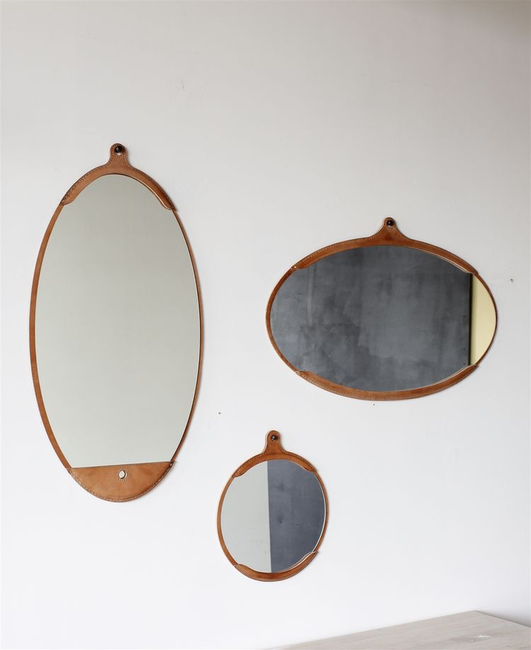 Leather-framed mirror in oval and circular shapes