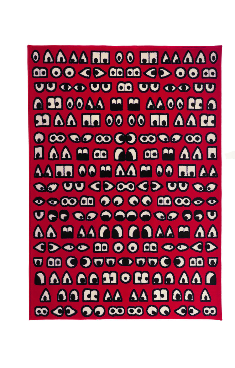 Red rug made up of black and white shapes, resembling eyes.