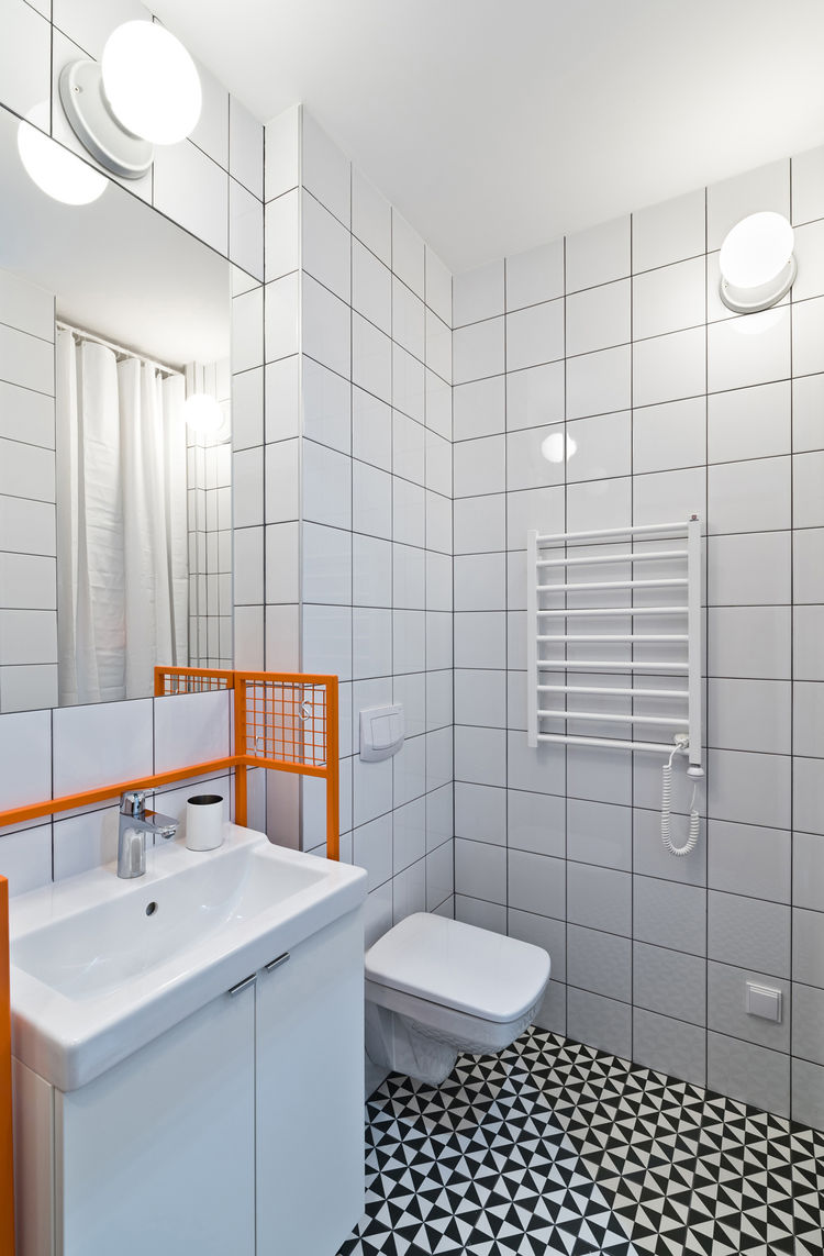 Graphic Vives floor tiles and custom-made orange sink frame.