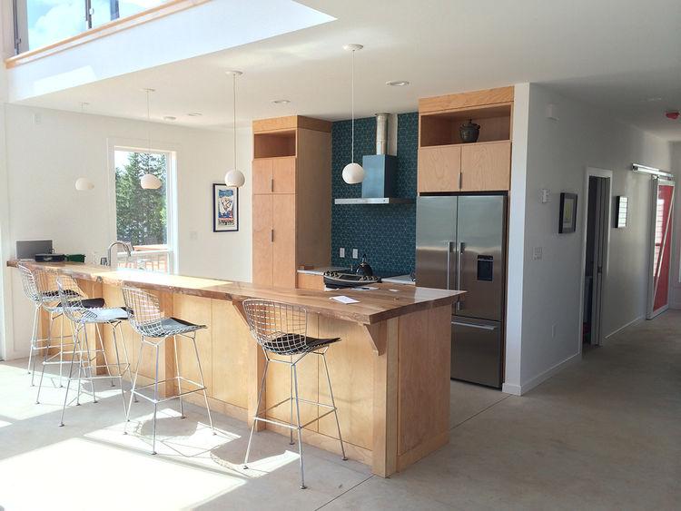 Raw edge maple island, Bertoia bar stools from Knoll, and Health tiles turquoise backsplash.