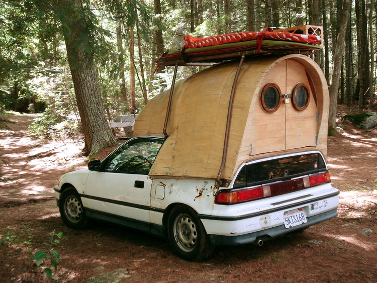 Tiny wood camper attached to a Honda Civic