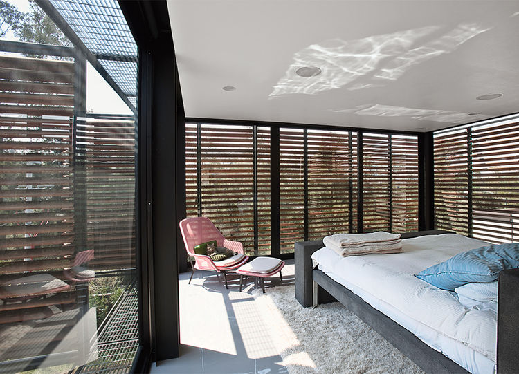 Bedroom with slatted window screens in a Mexico City home