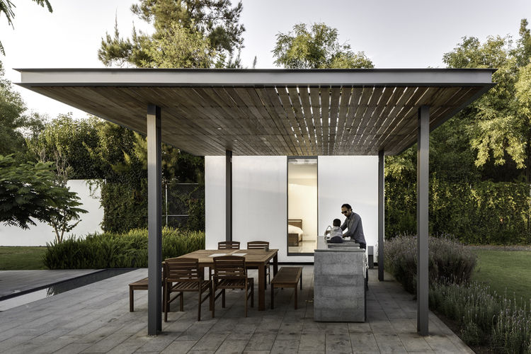 Outdoor dining shaded by tzalam wood of weekend home by Asociacion de Diseno in Mexico.