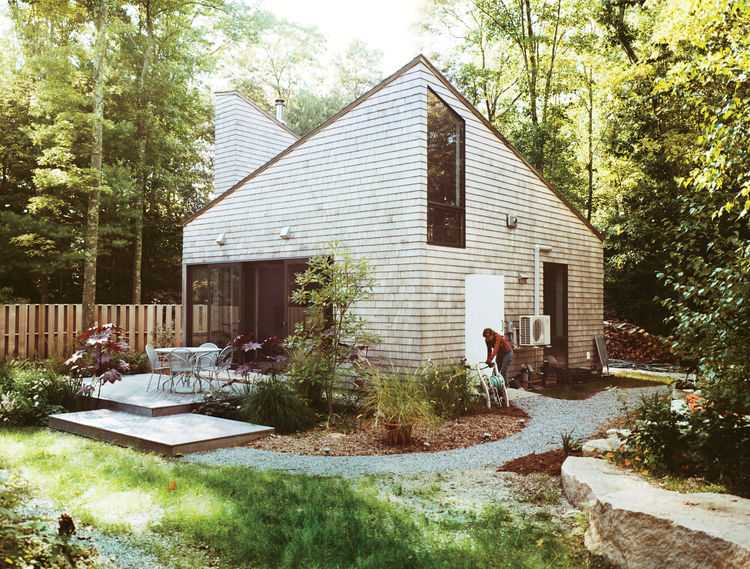 Modern small space Rhode Island cottage facade with windows, chimney, skylight and cedar cladding