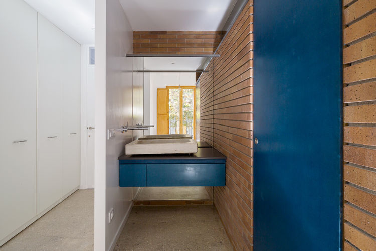Barcelona bathroom with brick and a blue vanity