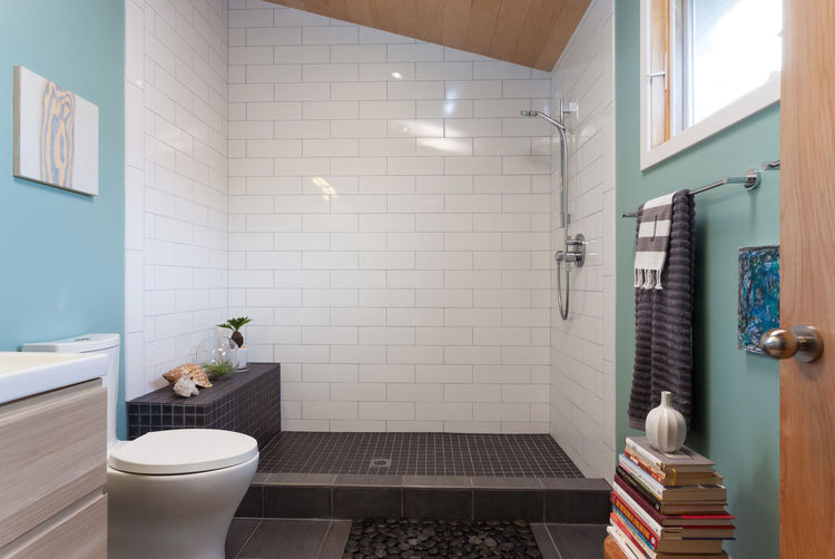 White tile bathroom with a rock garden