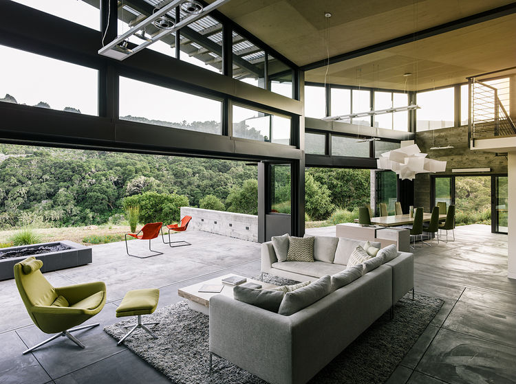Living and dining room of a modern eco-conscious pavilion in California by Feldman Architecture with Ligne Roset chairs Foscarini lighting and B&B Italia sofa.