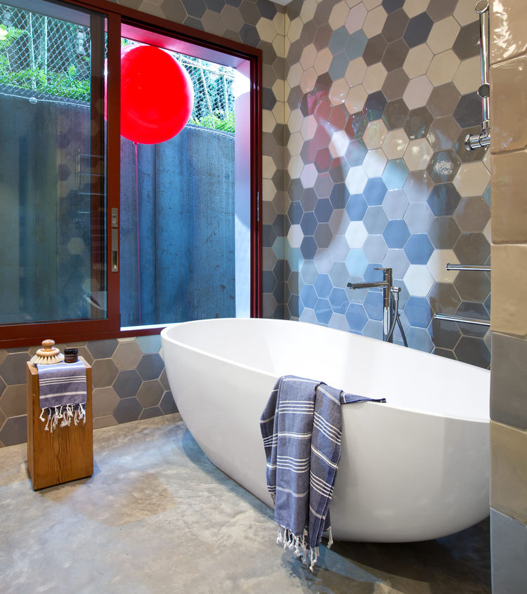A freestanding tub by Aquabrass is surrounded by hexagonal tiles in the master bathroom.