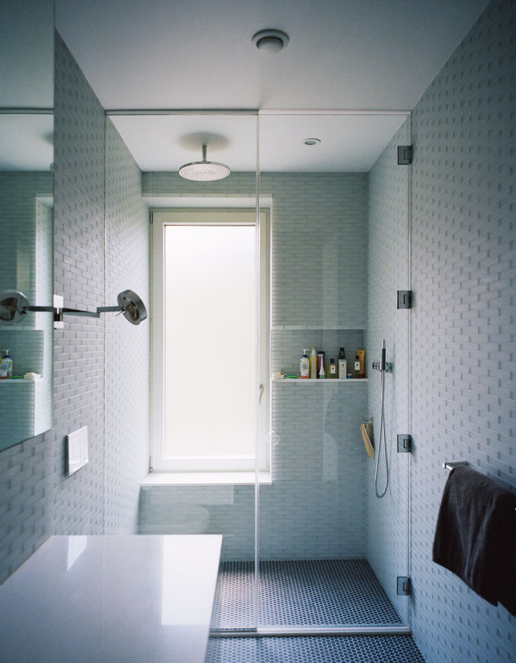 Triple-glazed, frosted windows emit filtered light in a master bathroom.