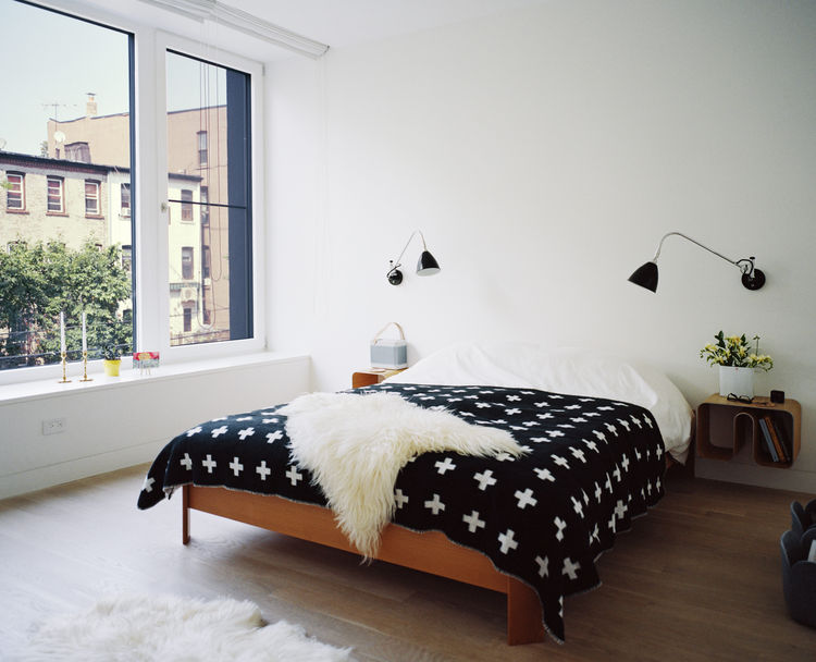The master bedroom includes a BoConcept bed and a HAY blanket by Pia Wallén.