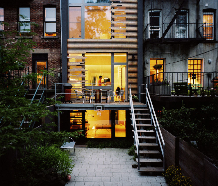 The facade in the backyard is made from wood slats.