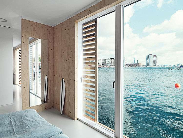 Glass doors open the bedroom up to the water