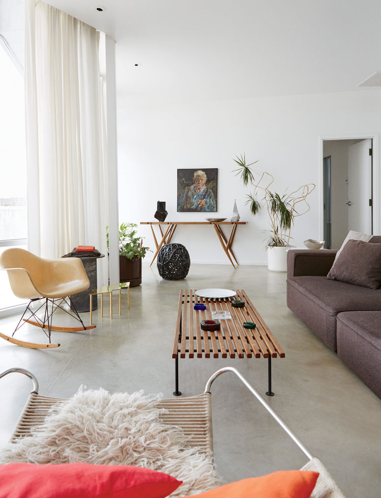 Mondern prefab Chicago live/work space by UrbanLab with Baldwin Kingrey coffee table, Eames rocker, Jonathan Muecke brass low table in the living area