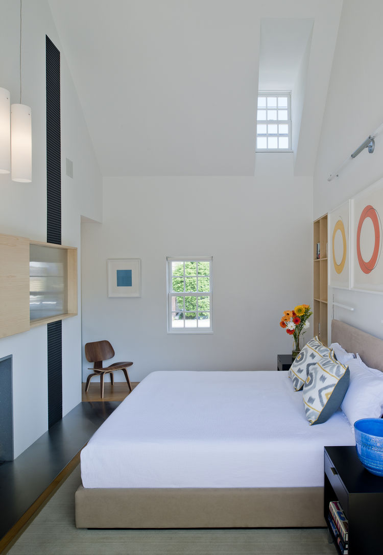 Custom bed and Eames molded plywood lounge chair in bedroom of Delaware renovation by Robert M. Gurney Architect