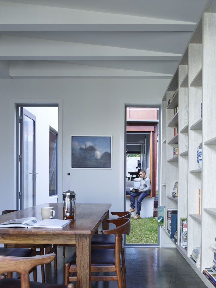 Dining room with white walls to maximize light in Brisbane home by O'Neill Architects.