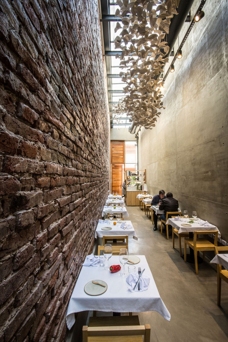 Modern restaurant with a brick wall and concrete floors