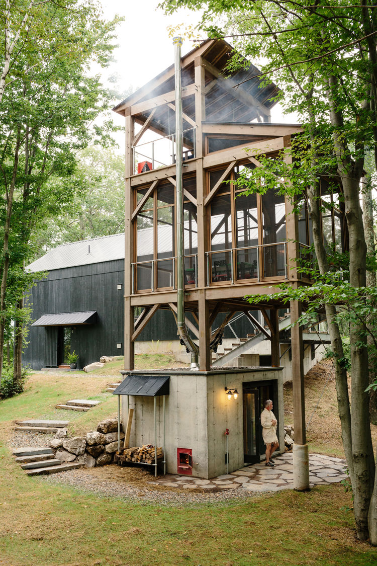 The surrounding landscape wraps around the house and a tower that features a sauna.