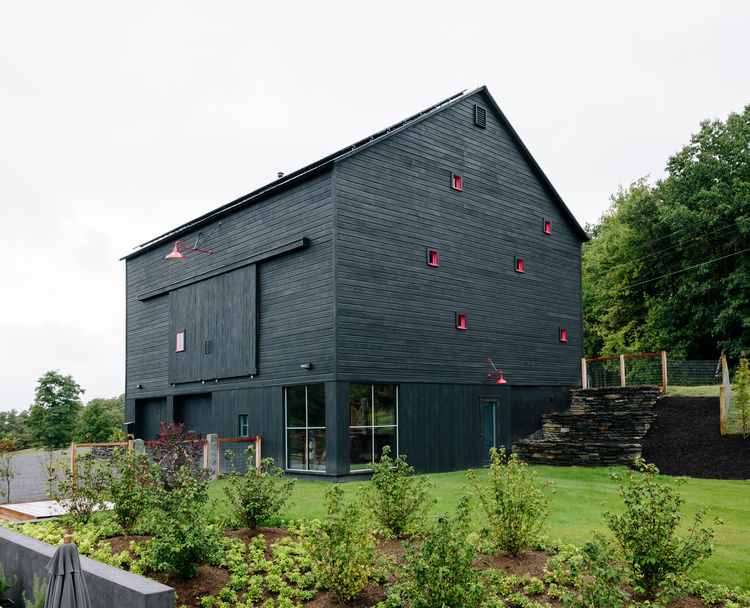 Red windows articulate the charred-wood facade of this Hudson Valley house.