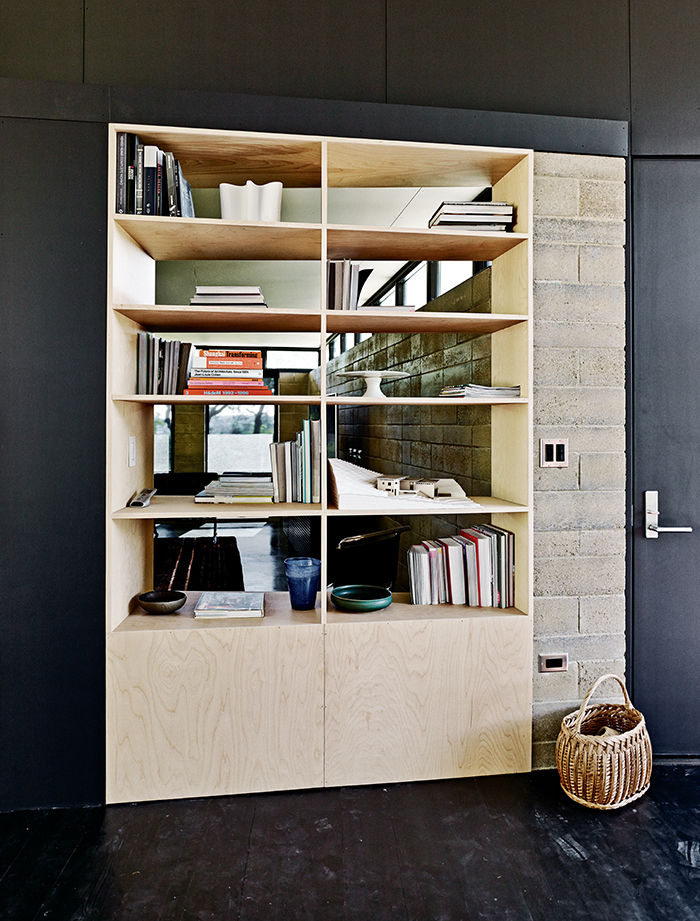 Rammed-earth home with birch-ply bookcase in the living room