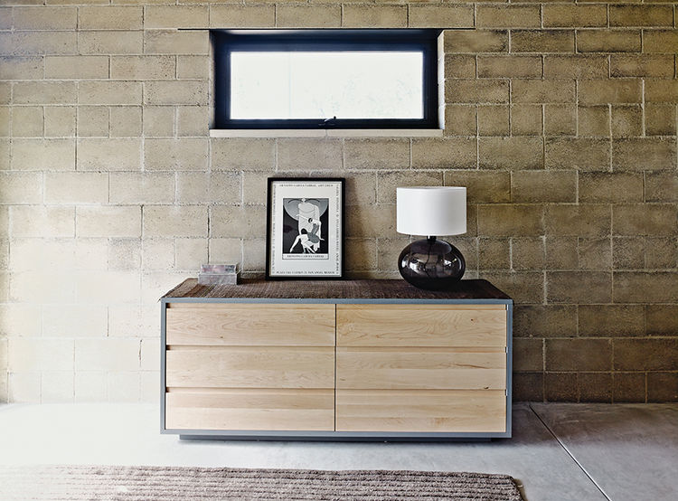 Rammed-earth home with Room & Board dresser in the master bedroom