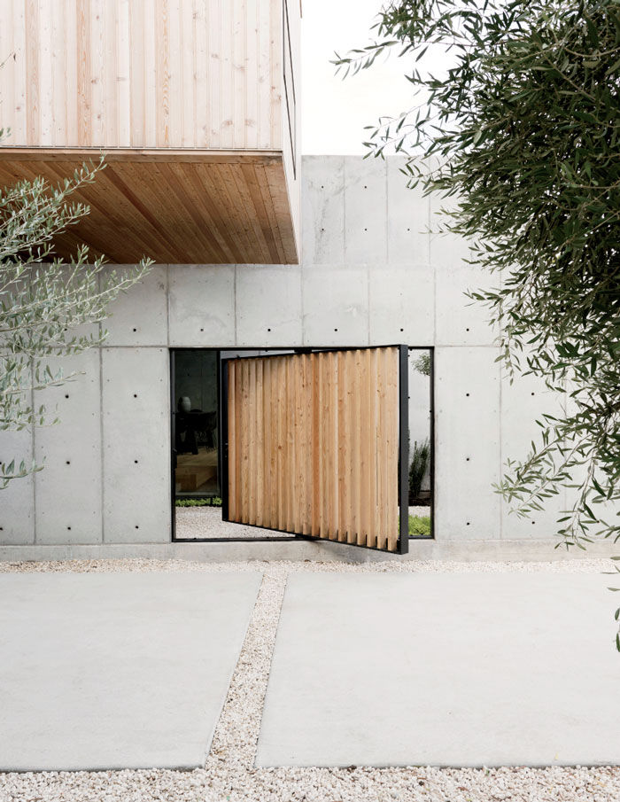 Modern Texas home facade with pivoting door of Siberian larch.