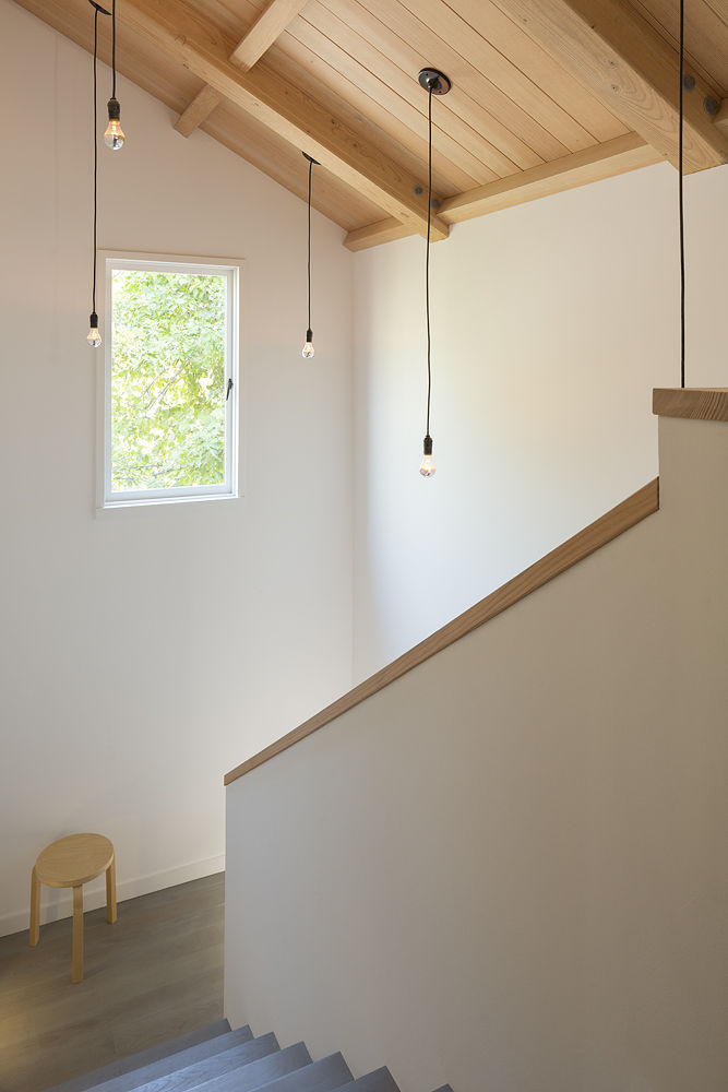 Stairs overhung by schoolhouse-style pendants
