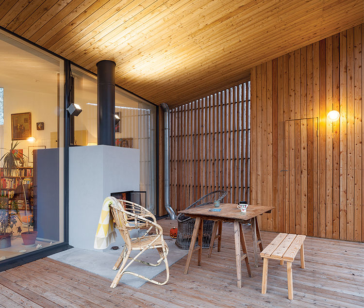 Modern home in Finland with sauna has rattan armchair and drafting table on outdoor terrace fireplace