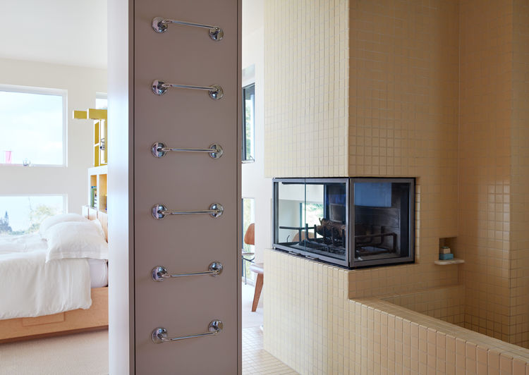 A ladder-like series of towel rungs mark the adjacent bathroom