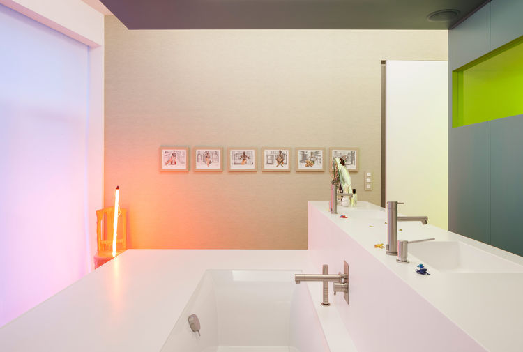 Corian sinks, Ritmonio fixtures, and glowing artwork in bathroom.