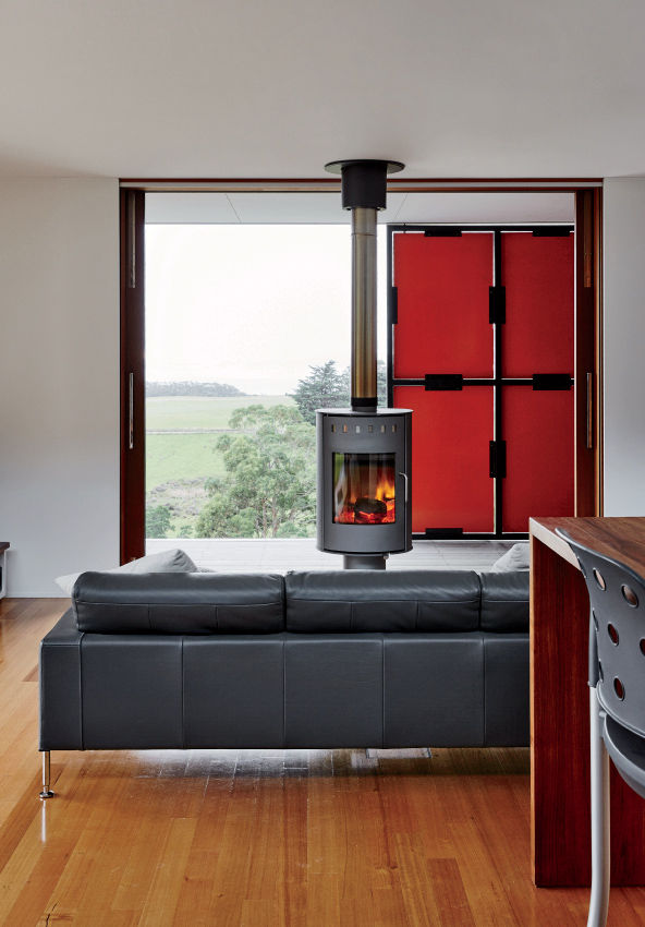 Rais fireplace adjacent veranda of off-the-grid Tasmanian prefab by Misho+Associates.