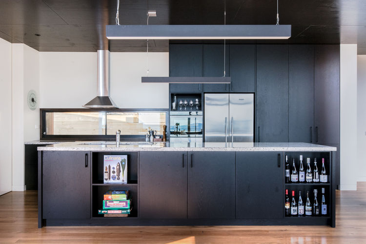 Kitchen with granite island countertop and Matric-P4 pendant lights from Lightnet in Australian beach home by OLA Studio