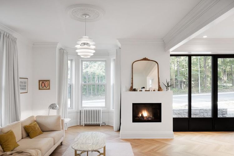 A PH Snowball light pendant by Louis Poulsen hangs in the living room with a gas fireplace by Foyer Universel.