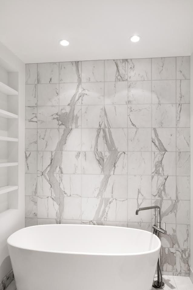 The master bathroom's Wetstyle bathtub, complete with a Kohler faucet, sits up against calacatta marble tiles on the wall.