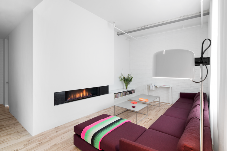 Deep purple sofa and a minimal fireplace