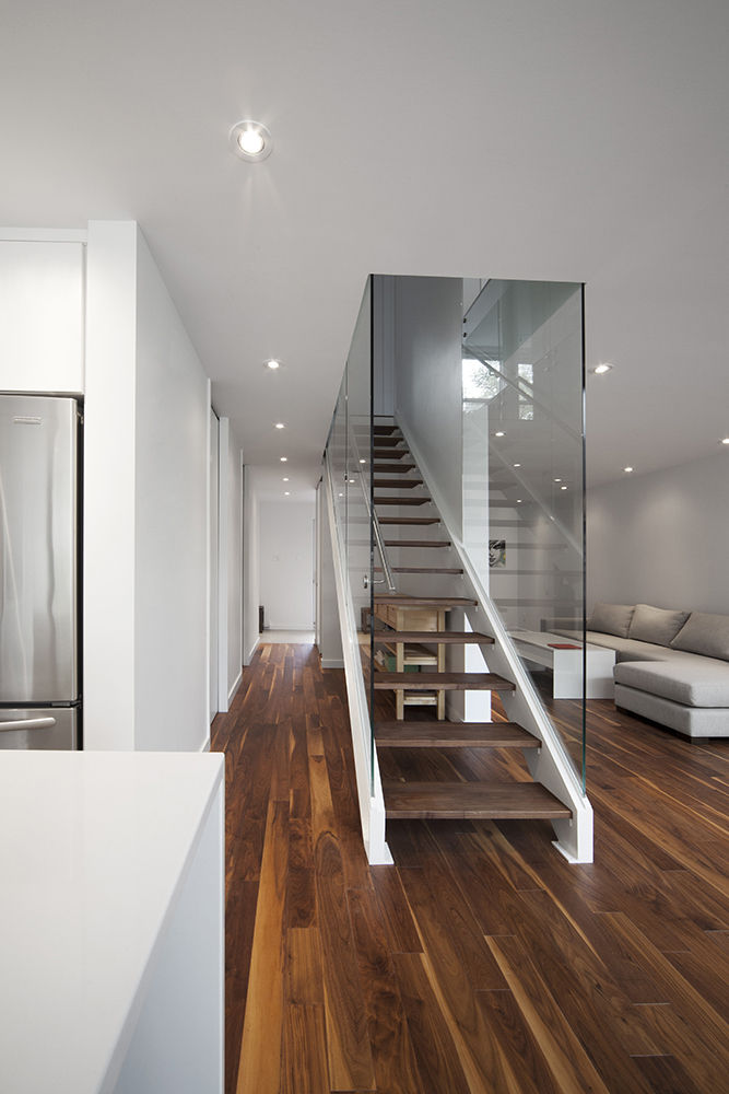 Stair with walnut treads and white steel in Montreal renovation by Blouin Tardif.