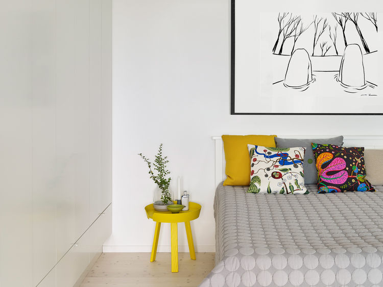 A bedroom with Hay's Mega Dot blanket and graphic pillows designed by Josef Frank for Svenskt Tenn