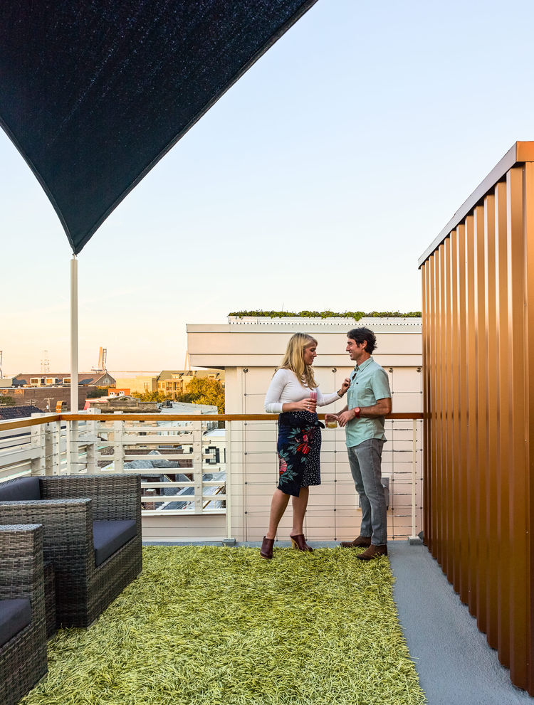 Two people share a drink during dusk on rustic deck.