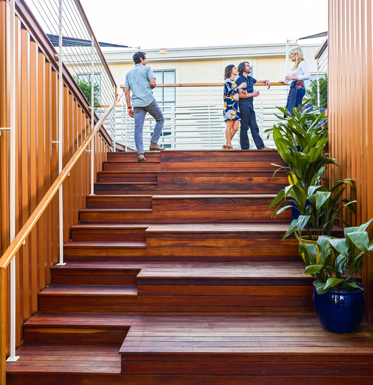 Friends gather on the wooden stair terrace at South Carolina home.